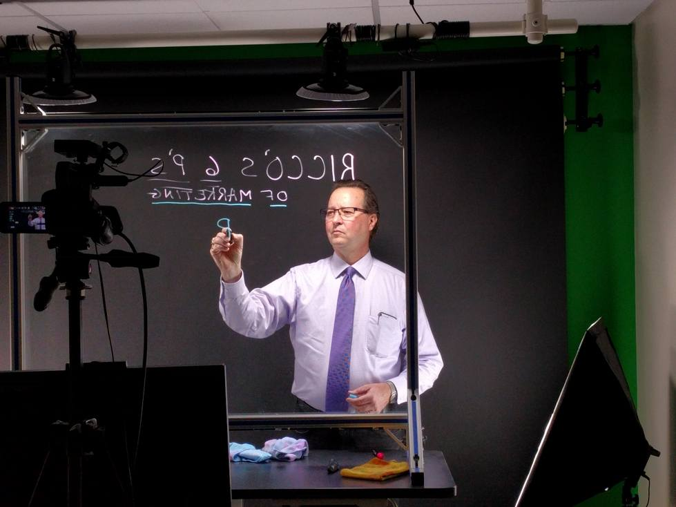 Professor using lightboard with camera filming them